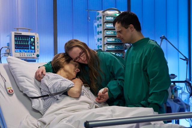 Carina Kühne als Manja Jokisch am Krankenbett von Karin Giegerich als Mutter und Addas Ahmad als Freund in grünen Krankenhauskitteln,